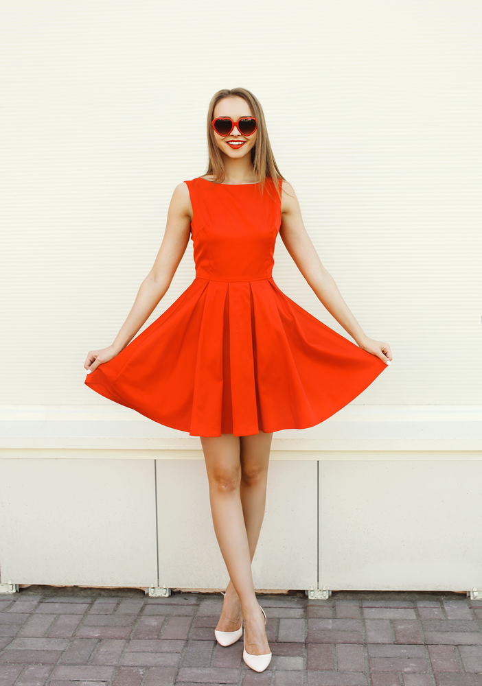 Pretty young woman in the red dress and heart sunglasses having
